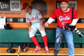 Kevin Frandsen of the Philadelphia Phillies jokes around in the dugout with photographer Michael Zagaris before the game against the San Francisco...
