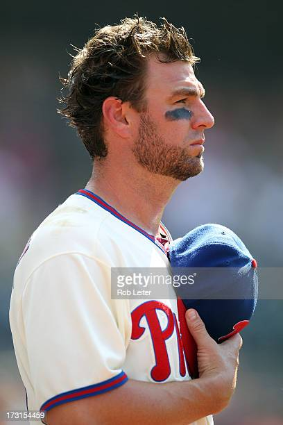 Kevin Frandsen of the Philadelphia Phillies salutes the flag before the game against the Milwaukee Brewers at Citizens Bank Park on June 1 2013 in...