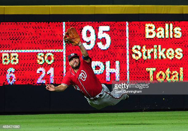 Kevin Frandsen of the Washington Nationals makes a diving catch in the eighth inning against the Atlanta Braves at Turner Field on August 9 2014 in...