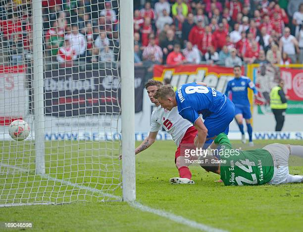Kevin Freiberger of Lotte scores his teams first goal against Kevin Grund and goalkeeper Daniel Schwabke of Essen during the Regionalliga West match...