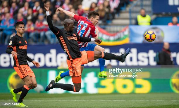 Kevin Gameiro of Atletico de Madrid competes for the ball with Eliaquim Hans Mangala of Valencia CF and his teammate Joao Cancelo during the match...