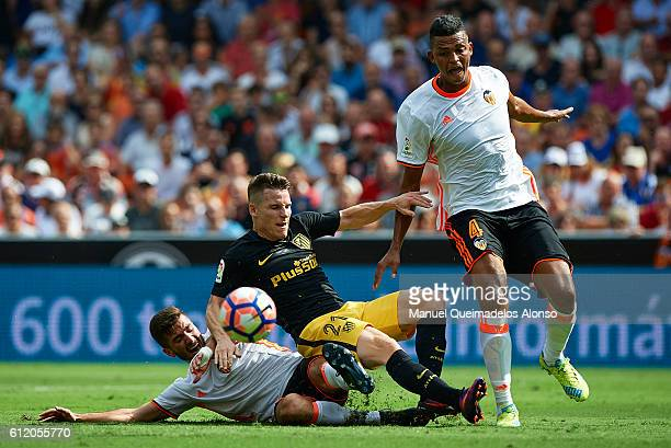 Kevin Gameiro of Atletico de Madrid is tackled by Jose Luis Gaya and Aderlan Santos of Valencia during the La Liga match between Valencia CF and...