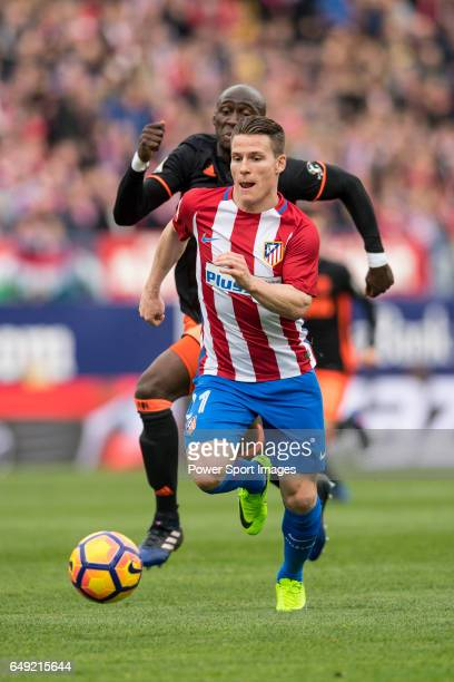 Kevin Gameiro of Atletico de Madrid runs with the ball while Eliaquim Hans Mangala of Valencia CF is in pursuit during the match Atletico de Madrid...