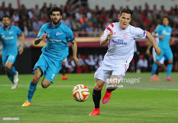 Kevin Gameiro of Sevilla and Luis Neto of Zenit St Petersburg chase the ball during the UEFA Europa League Quarter Final first leg match between FC...