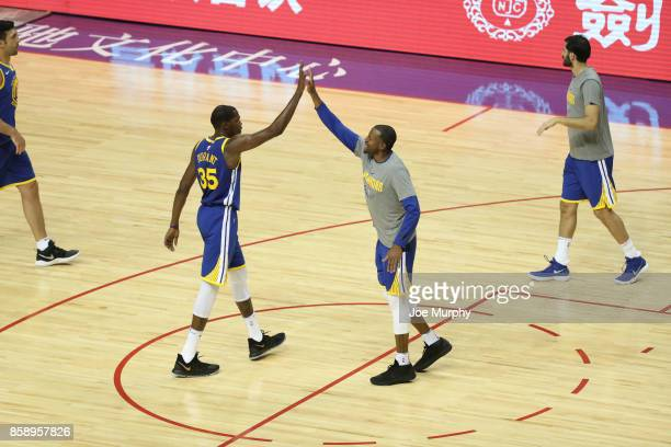 Kevin Garnett and Andre Iguodala of the Golden State Warriors high fives against the Minnesota Timberwolves as part of the 2017 Global Games China on...