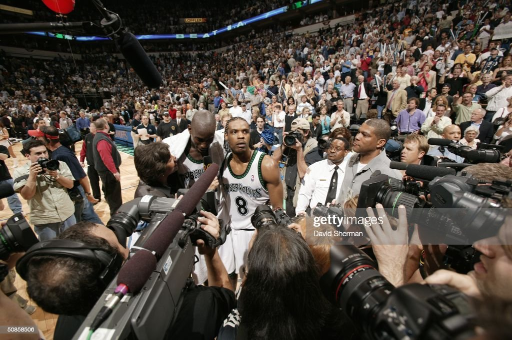 Kevin Garnett #21 and Latrell Sprewell #8 of the Minnesota Timberwolves give a post game interview with Cheryl Miller of TNT as they are surrounded by fans and media after the winning game seven against the Sacramento Kings in Game Seven of the Western Conference Semifinals during the 2004 NBA Playoffs at Target Center on May 19, 2004 in Minneapolis, Minnesota.