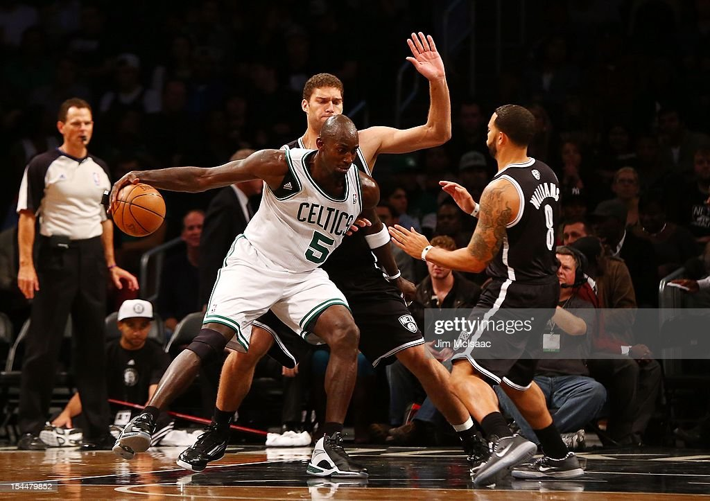 Kevin Garnett #5 of the Boston Celtics in action against Brook Lopez #11 and Deron Williams #8 of the Brooklyn Nets during a preseason game at the Barclays Center on October 18, 2012 in the Brooklyn borough of New York City. The Celtics defeated the Nets 115-85.