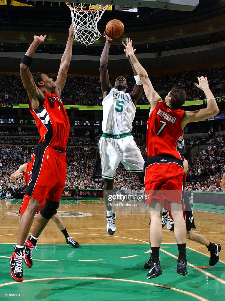 Kevin Garnett #5 of the Boston Celtics takes a shot against Andrea Bargnani #7 and Chris Bosh #4 of the Toronto Raptors on January 23, 2008 at the TD Banknorth Garden in Boston, Massachusetts.