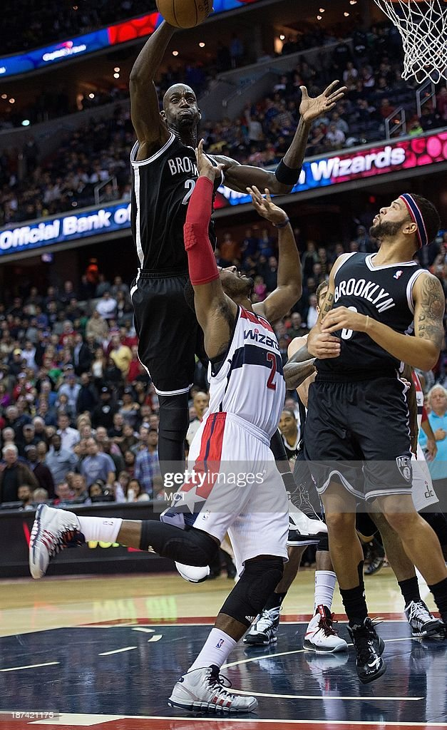 Kevin Garnett (2) of the Brooklyn Nets blocks the shot of John Wall (2) of the Washington Wizards as Deron Williams (8) of Brooklyn avoids contact with Wall during the second half of their game played at the Verizon Center in Washington, Friday, November 8, 2013. Washington defeated Brooklyn 112-108.