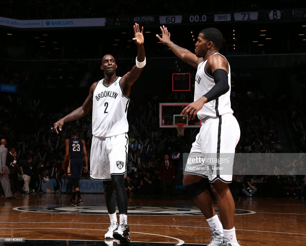 Kevin Garnett #2 of the Brooklyn Nets gets a high-five from teammate Joe Johnson #7 during a game against the New Orleans Pelicans at the Barclays Center on February 9, 2014 in the Brooklyn borough of New York City.
