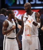 Kevin Garnett of the Brooklyn Nets talks with Tyshawn Taylor following a timeout during the second half against the Denver Nuggets at Barclays Center...