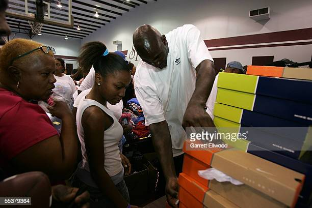 Kevin Garnett of the Minnesota Timberwolves checks sizes of sneakers to hand out to evacuees of Hurricane Katrina during Kenny Smith's Hurricane...
