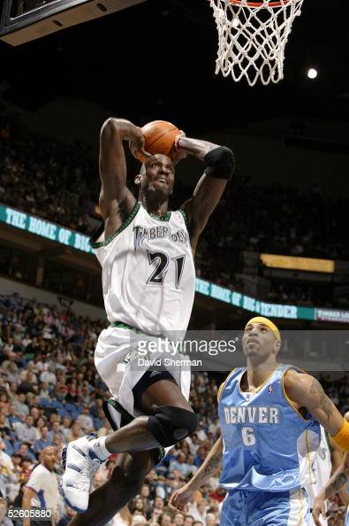 Kevin Garnett of the Minnesota Timberwolves goes up for the slam dunk over Kenyon Martin of the Denver Nuggets on April 8 2005 at the Target Center...