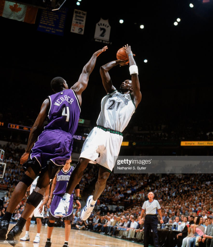 Kevin Garnett #21 of the Minnesota Timberwolves puts a shot up against Chris Webber #4 of the Sacramento Kings in Game Seven of the Western Conference Semifinals during the 2004 NBA Playoffs at Target Center on May 19, 2004 in Minneapolis, Minnesota. The Timberwolves won 83-80.
