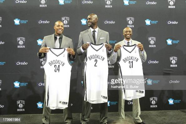 Kevin Garnett Paul Pierce and Jason Terry of the Brooklyn Nets pose with their new jerseys during a press conference at the Barclays Center on July...