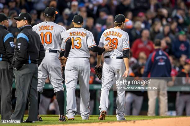 Kevin Gausman of the Baltimore Orioles exits the game alongside Manny Machado and Adam Jones after being ejected from the game for hitting Xander...