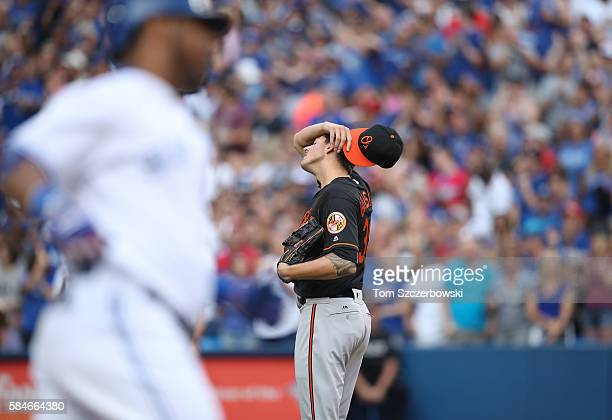 Kevin Gausman of the Baltimore Orioles reacts after giving up a solo home run to Edwin Encarnacion of the Toronto Blue Jays who circles the bases in...