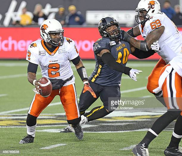 Kevin Glenn of the BC Lions looks to make a pass while being pursued by Eric Norwood of the Hamilton Tigercats in a CFL football game at Tim Hortons...