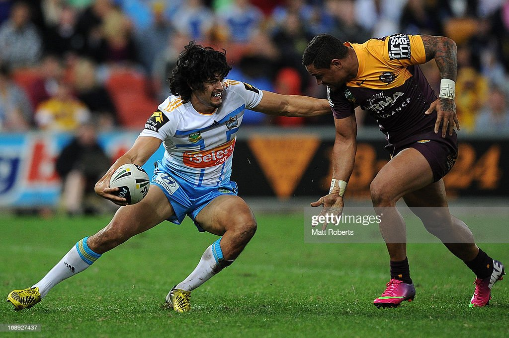 Kevin Gordon of the titans fends off the defence during the round 10 NRL match between the Brisbane Broncos and the Gold Coast Titans at Suncorp Stadium on May 17, 2013 in Brisbane, Australia.