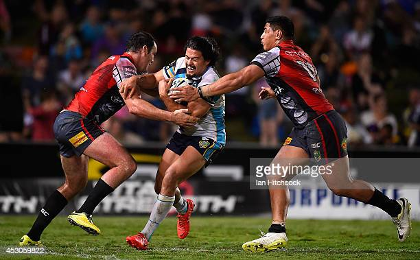 Kevin Gordon of the Titans is tackled by Kane Linnett and Jason Taumalolo of the Cowboys during the round 21 NRL match between the North Queensland...