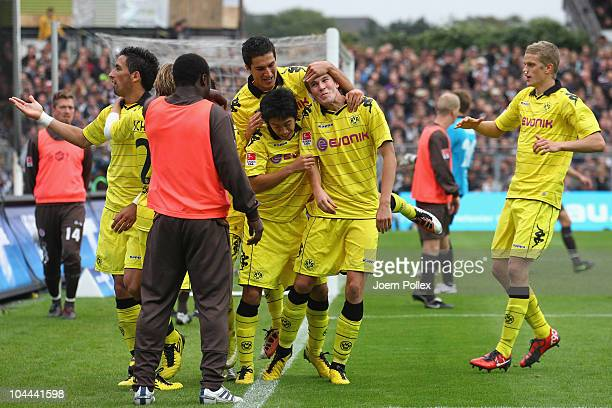 Kevin Grosskreutz of Dortmund celebrates with his team mates after scoring his team's third goal and while Gerals Asamoah of St Pauli warms up during...
