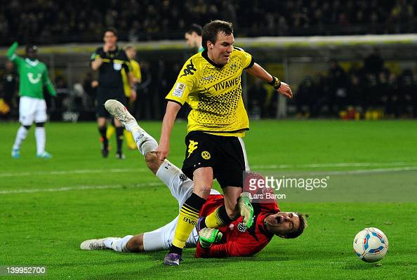 Kevin Grosskreutz of Dortmund is challenged by goalkeeper Ron Robert Zieler of Hannover during the Bundesliga match between Borussia Dortmund and...