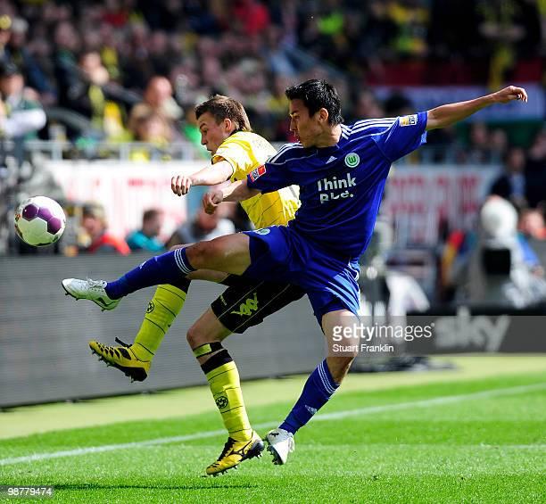 Kevin Grosskreutz of Dortmund is challenged by Makoto Hasebe of Wolfsburg during the Bundesliga match between Borussia Dortmund and VfL Wolfsburg at...