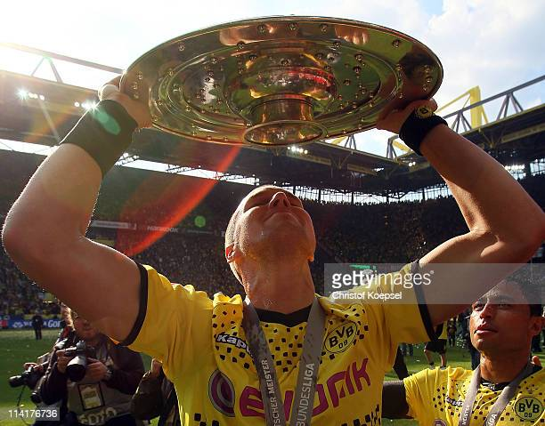 Kevin Grosskreutz of Dortmund lifts the German Championship trophy on the podium after the Bundesliga match between Borussia Dortmund and Eintracht...