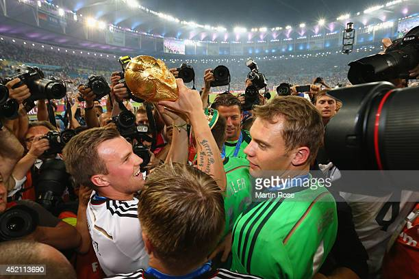 Kevin Grosskreutz of Germany raises the World Cup trophy with teammates after defeating Argentina 10 in extra time during the 2014 FIFA World Cup...