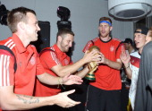 Kevin Grosskreutz Shkodran Mustafi Per Mertesacker and Bastian Schweinsteiger of Germany pose with the World Cup trophy as they celebrate with...