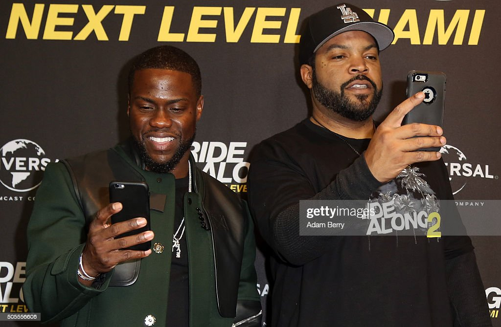 Kevin Hart and Ice Cube take pictures with their mobile phones during a photo call for the film 'Ride Along Next Level Miami' at Kino in der...