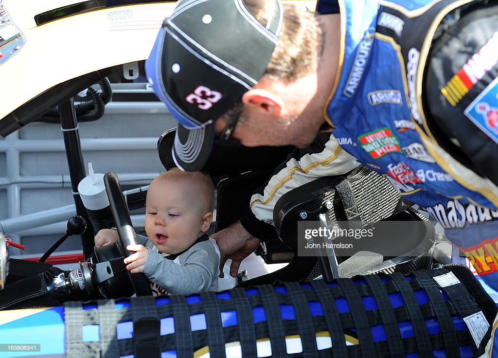 Kevin Harvick, driver of the #33 Armour Chevrolet, puts his son Keelan in his car on the grid prior to the NASCAR Nationwide Series Jeff Foxworthy's Grit Chips 300 at Bristol Motor Speedway on March 16, 2013 in Bristol, Tennessee.