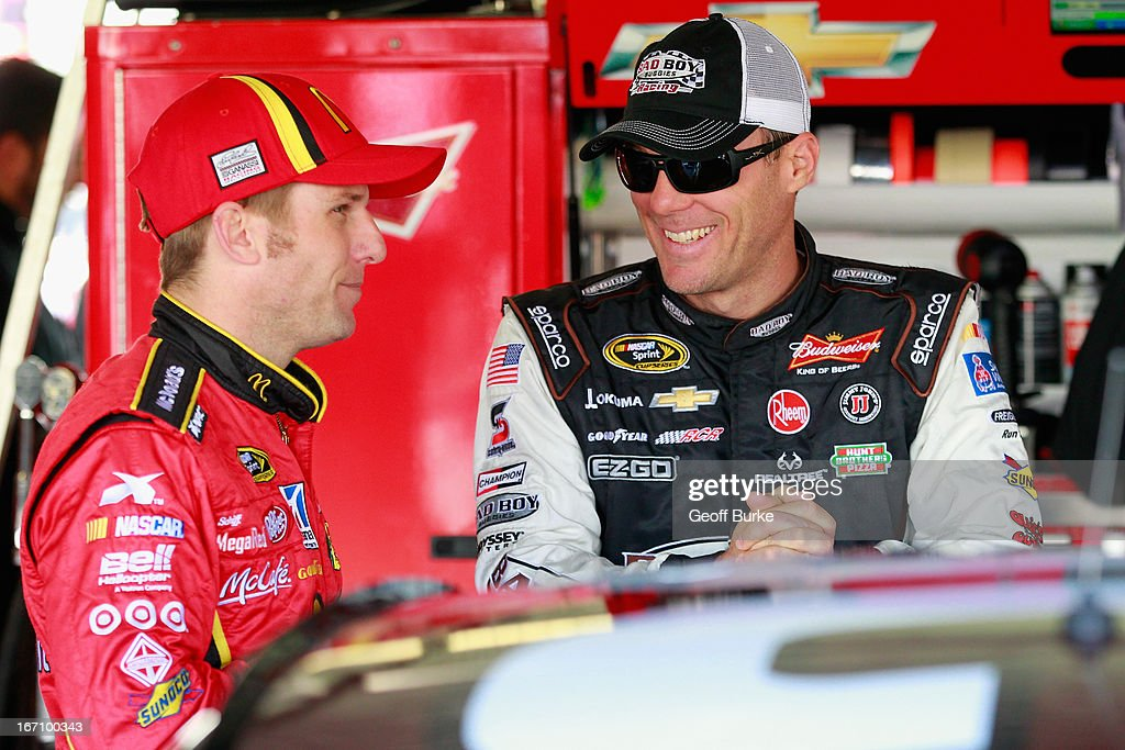 Kevin Harvick (r), driver of the #29 Bad Boy Buggies Chevrolet, talks with Jamie McMurray (l), driver of the #1 McDonald's Chevrolet, in the garage prior to practice for the NASCAR Sprint Cup Series STP 400 at Kansas Speedway on April 20, 2013 in Kansas City, Kansas.