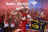 Kevin Harvick driver of the Budweiser Chevrolet celebrates in Victory Lane after winning the NASCAR Sprint Cup Series Bank of America 500 at...