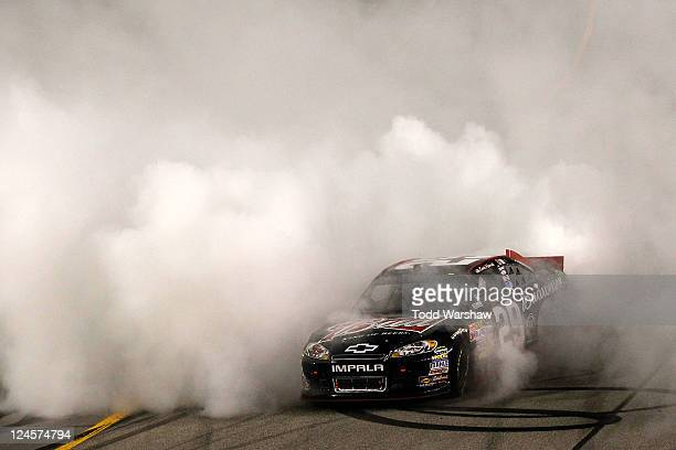 Kevin Harvick driver of the Budweiser Chevrolet celebrates with a burnout after winning the NASCAR Sprint Cup Series Wonderful Pistachios 400 at...