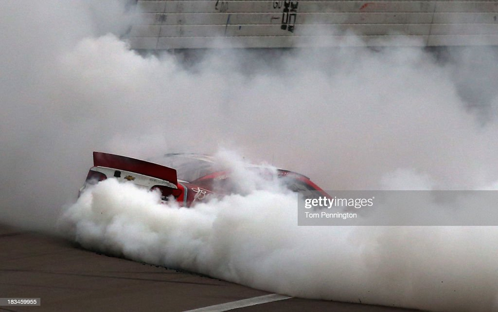 Kevin Harvick, driver of the #29 Budweiser Chevrolet, celebrates with a burnout after winning the NASCAR Sprint Cup Series 13th Annual Hollywood Casino 400 at Kansas Speedway on October 6, 2013 in Kansas City, Kansas.