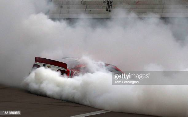 Kevin Harvick driver of the Budweiser Chevrolet celebrates with a burnout after winning the NASCAR Sprint Cup Series 13th Annual Hollywood Casino 400...