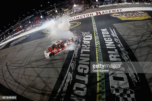 Kevin Harvick driver of the Budweiser Chevrolet celebrates with a burnout after winning the NASCAR Sprint Cup Series Bojangles' Southern 500 at...