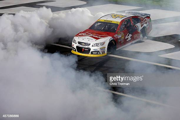 Kevin Harvick driver of the Budweiser Chevrolet celebrates with a burnout after winning the NASCAR Sprint Cup Series Bank of America 500 at Charlotte...