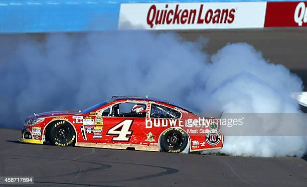 Kevin Harvick driver of the Budweiser Chevrolet celebrates with a burnout after winning the NASCAR Sprint Cup Series Quicken Loans Race for Heroes...