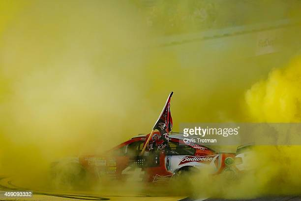 Kevin Harvick driver of the Budweiser Chevrolet celebrates with a burnout after winning the NASCAR Sprint Cup Series Ford EcoBoost 400 at...