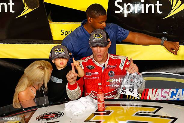 Kevin Harvick driver of the Budweiser Chevrolet celebrates with his wife DeLana and son Keelan in victory lane after winning during the NASCAR Sprint...