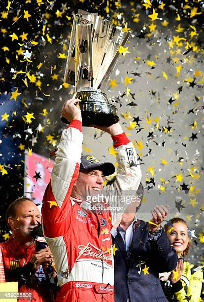 Kevin Harvick driver of the Budweiser Chevrolet celebrates with the trophy in Victory Lane after winning the NASCAR Sprint Cup Series Ford EcoBoost...