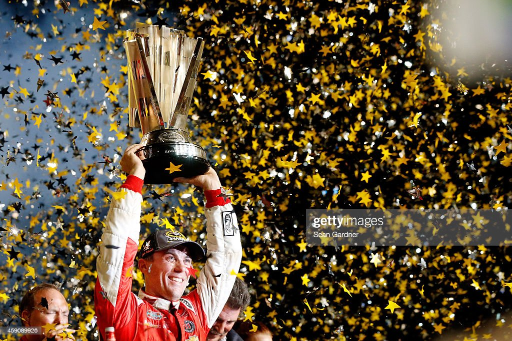 <a gi-track='captionPersonalityLinkClicked' href=/galleries/search?phrase=Kevin+Harvick&family=editorial&specificpeople=209186 ng-click='$event.stopPropagation()'>Kevin Harvick</a>, driver of the #4 Budweiser Chevrolet, celebrates with the trophy in Victory Lane after winning the NASCAR Sprint Cup Series Ford EcoBoost 400 and the NASCAR Sprint Cup Series Championship at Homestead-Miami Speedway on November 16, 2014 in Homestead, Florida.