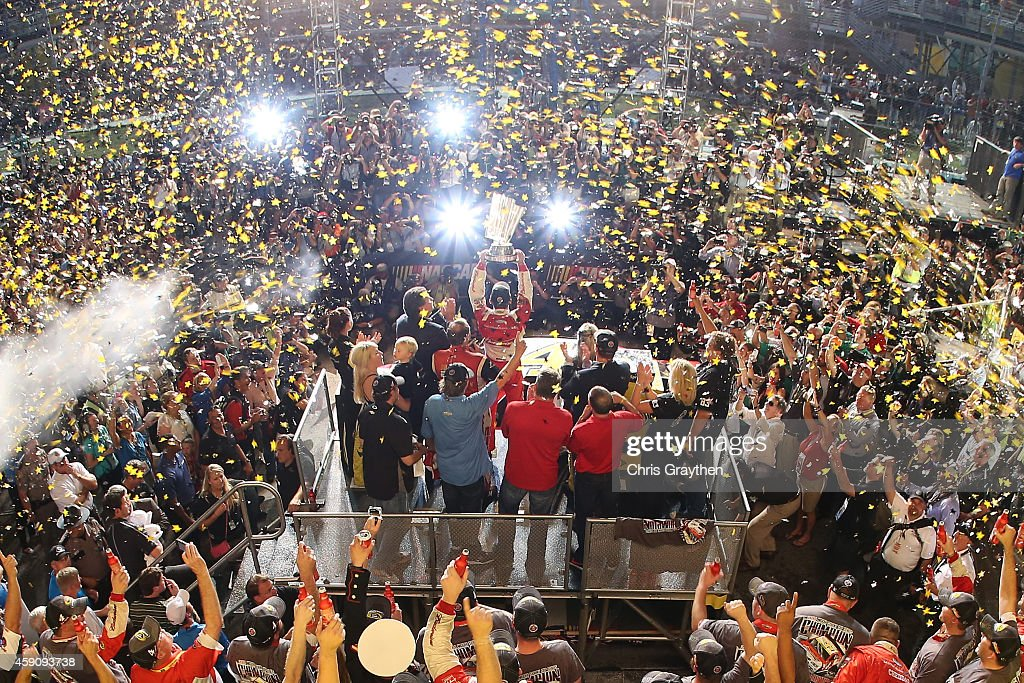 Kevin Harvick driver of the Budweiser Chevrolet celebrates with the trophy in victory lane after winning during the NASCAR Sprint Cup Series Ford...