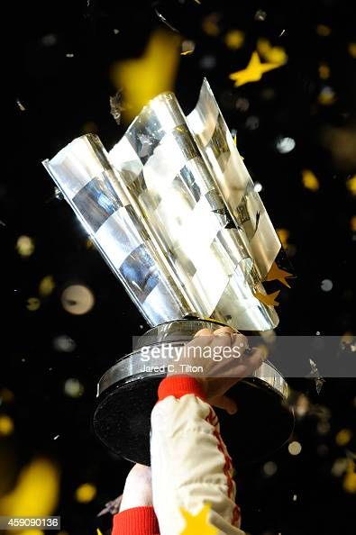 Kevin Harvick driver of the Budweiser Chevrolet holds up the trophy in Victory Lane after winning during the NASCAR Sprint Cup Series Ford EcoBoost...