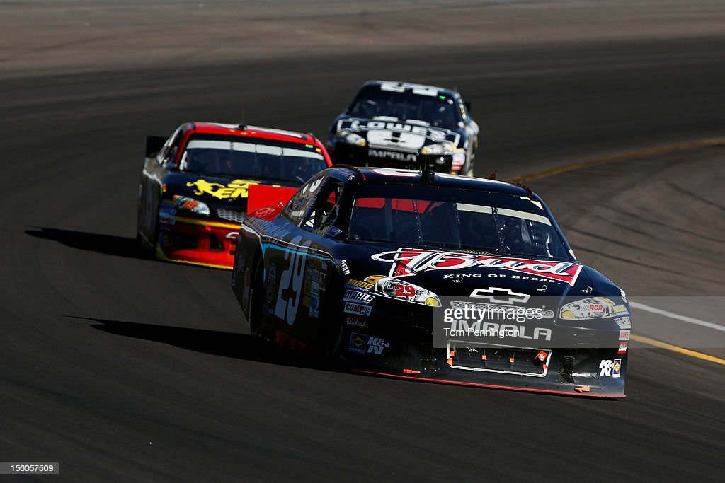 <a gi-track='captionPersonalityLinkClicked' href=/galleries/search?phrase=Kevin+Harvick&family=editorial&specificpeople=209186 ng-click='$event.stopPropagation()'>Kevin Harvick</a>, driver of the #29 Budweiser Chevrolet, leads <a gi-track='captionPersonalityLinkClicked' href=/galleries/search?phrase=Clint+Bowyer&family=editorial&specificpeople=537951 ng-click='$event.stopPropagation()'>Clint Bowyer</a>, driver of the #15 5-hour Energy Toyota, and <a gi-track='captionPersonalityLinkClicked' href=/galleries/search?phrase=Jimmie+Johnson+-+Pilota+Nascar&family=editorial&specificpeople=171519 ng-click='$event.stopPropagation()'>Jimmie Johnson</a>, driver of the #48 Lowe's/Kobalt Tools Chevrolet, during the NASCAR Sprint Cup Series AdvoCare 500 at Phoenix International Raceway on November 11, 2012 in Avondale, Arizona.