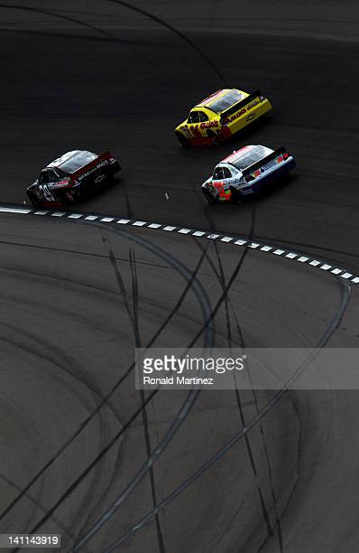 Kevin Harvick driver of the Budweiser Chevrolet leads Dave Blaney driver of the Ollie's Bargain Outlet Chevrolet and Ken Schrader driver of the...