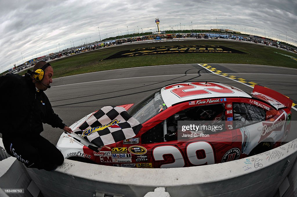<a gi-track='captionPersonalityLinkClicked' href=/galleries/search?phrase=Kevin+Harvick&family=editorial&specificpeople=209186 ng-click='$event.stopPropagation()'>Kevin Harvick</a>, driver of the #29 Budweiser Chevrolet, retrieves the checkered flag after winning the NASCAR Sprint Cup Series 13th Annual Hollywood Casino 400 at Kansas Speedway on October 6, 2013 in Kansas City, Kansas.