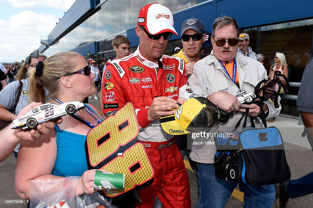 <a gi-track='captionPersonalityLinkClicked' href=/galleries/search?phrase=Kevin+Harvick&family=editorial&specificpeople=209186 ng-click='$event.stopPropagation()'>Kevin Harvick</a>, driver of the #4 Budweiser Chevrolet, signs his autograph for fans in the garage area during qualifying for the NASCAR Sprint Cup Series Quicken Loans 400 at Michigan International Speedway on June 13, 2014 in Brooklyn, Michigan.